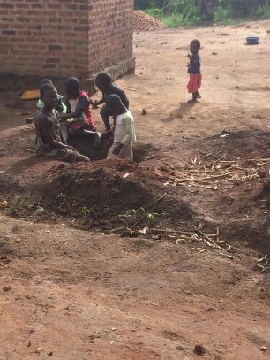 The children play in the big hole dug to plant matoki banana seedlings