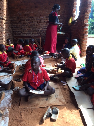 Working in one of the brick classrooms. Some children wait for their classmates to complete their necklaces