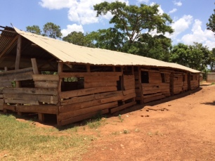 These are the open-sided rough wood classrooms with dry mud floors where the younger children have their lessons. No protection from the terrible dust!