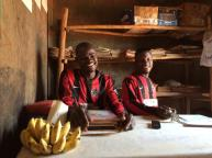 Ibrahim and Innocent in the school office, exercise books behind. Ibrahim bought me delicious sweet bananas!